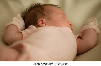 Newborn. Baby girl sleeping. Two weeks old. Close-up.