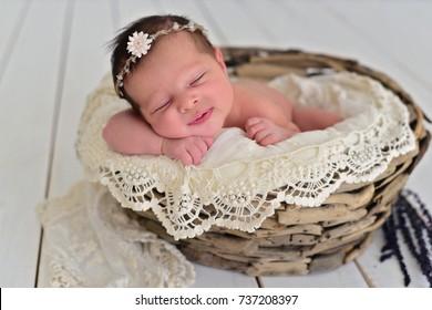 Newborn baby girl sleeping in wooden basket. Newborn photography.