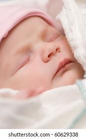 A newborn baby girl sleeps contentedly.