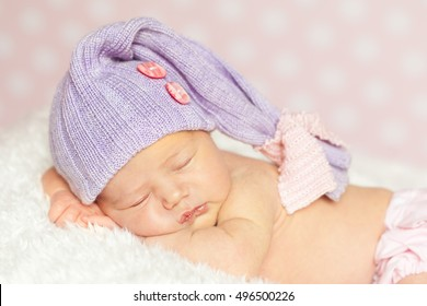 Newborn baby girl in a violet hat and lace panties sleeping on a soft white fur