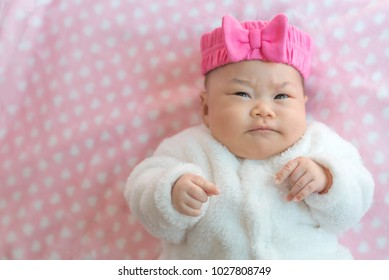 Newborn baby girl wear sweater and pink headband  on a bed