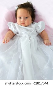 Newborn baby girl in a white baptism dress on a pink blanket