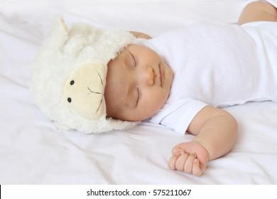 Newborn baby girls sleep and wearing white sheep or lamb hats