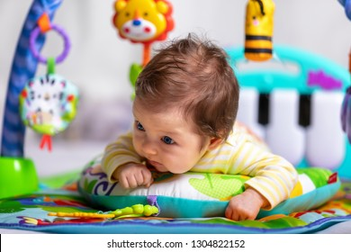 Newborn baby has tummy time training at it's colorful baby gym