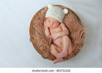 Newborn baby in hat in basket on brown background