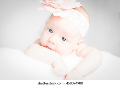 Newborn baby with headband on the head lying on blanket. Cute baby girl.