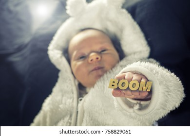 Newborn baby holding up a golden knuckle duster that reads the word BOOM.