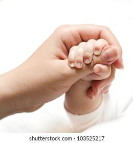 Newborn baby holding mother hand.