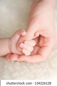 Newborn baby holding mothers finger