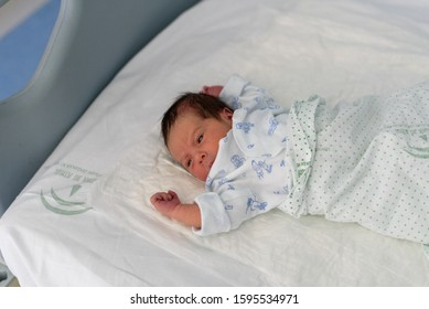 newborn baby in a hospital crib with a baby blanket