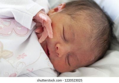 Newborn baby laying in the bed sleeping. Birth concept.