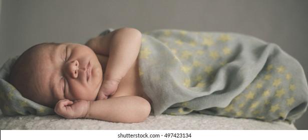 A newborn baby is laying down sleeping.