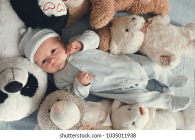 newborn baby laying with five teddy bears on blanket