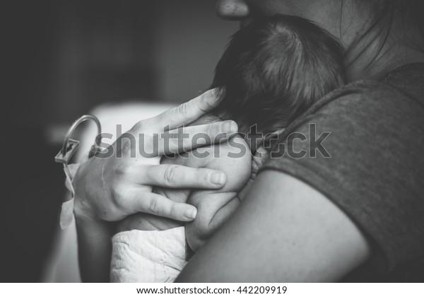 Bebé recién nacido tirado en el pecho de su mamá en el hospital
