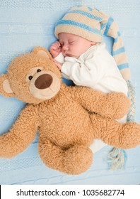 newborn baby laying with teddy bear on blanket