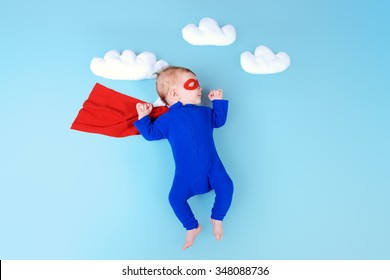Newborn baby. Little super hero flying through the sky.