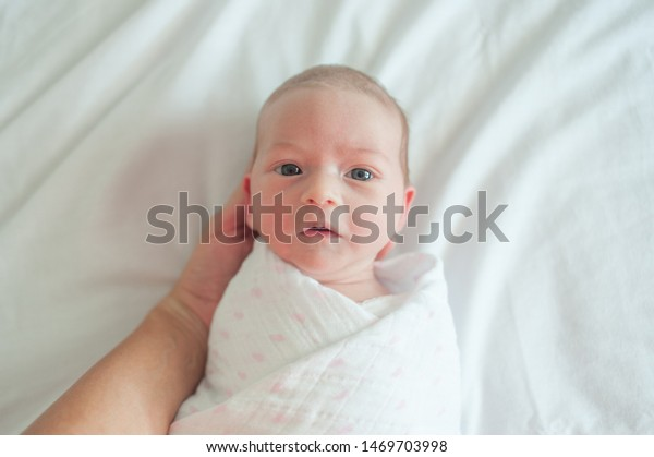 Newborn baby looking at camera