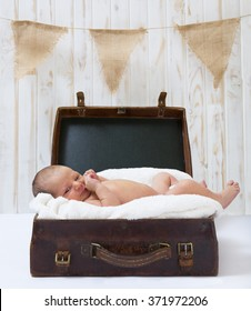 Newborn baby lying in a brown vintage suitcase on a white blanket looking at the camera