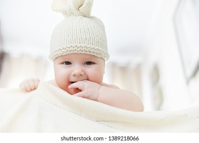A newborn baby is lying on a soft bed. Children's emotions.