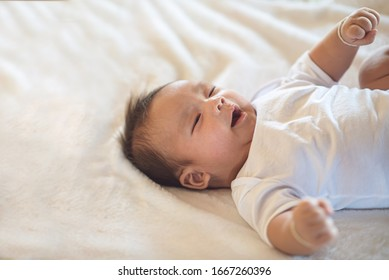 Newborn baby lying on a soft white mattress, smiling happily.