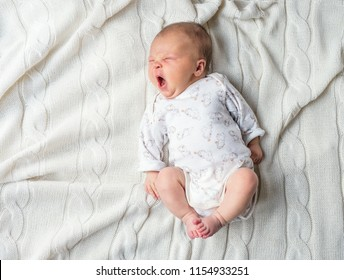 Newborn baby lying on a white blanket, yawning. Top view.