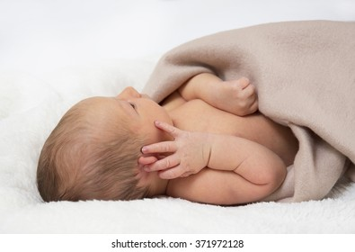 Newborn baby lying on a white blanket underneath a tan colour blanket