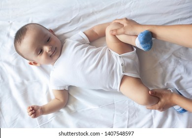 Newborn baby massage. Mom doing gymnastics with kid. Mommy massaging her cute baby boy. Moving a baby's legs, relieve constipation. Mother doing exercises and movements to stimulate a baby's bowels.
