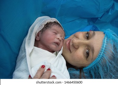 Newborn baby with mother in hospital, seconds after birth.