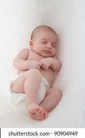 Newborn Baby on a white background. Hanging in cotton sling.
