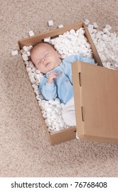 Newborn baby in open post box with filler on carpet