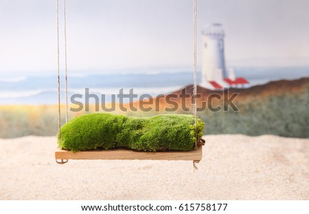 A newborn baby photography backdrop prop of a moss covered swing and the beach with a lighthouse and ocean waves in the background.