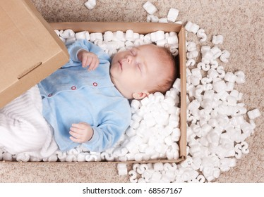 Newborn baby represented in post box with filler. Small baby sleeping among filler. Little newborn baby will be delivered to his parents.