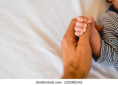 Newborn baby securely grasping his mother's hands, close-up fingers.