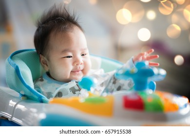 Newborn baby sit on walking training car with bubble soft, Asian baby smile on toy car.