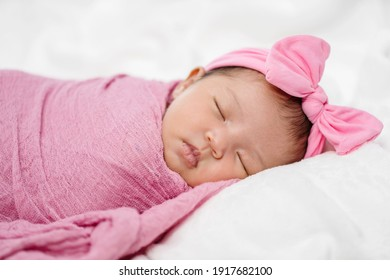 newborn baby sleep in pink cloth wrap blanket on a bed