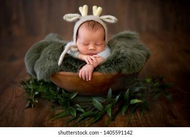 Newborn baby sleeping in an antique brown wooden bowl