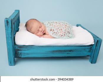Newborn baby sleeping, asleep on bed