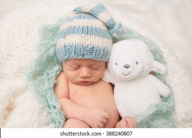 Newborn Baby sleeping, asleep with a stuffed toy, on a blanket, wearing a knit hat