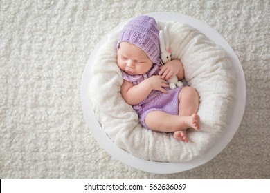 Newborn baby sleeping in a bed with a plush hare
