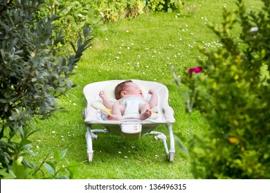 Newborn baby sleeping in a bouncer in the garden