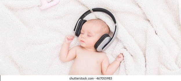 Newborn baby sleeping in a fluffy blanket, wearing headphones