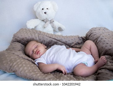 Newborn baby sleeping full length with white teddy bear in background