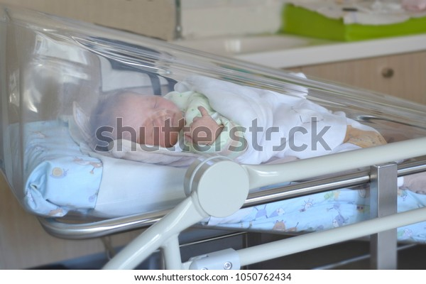 Newborn baby sleeping in the hospital bed