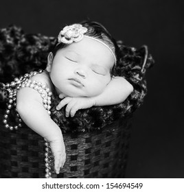 Newborn baby  sleeping inside a basket, resting on arms and elbows, on background. Wearing pearls and flower headband. Black and white.