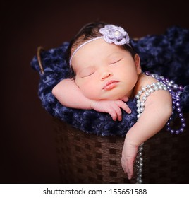 Newborn baby  sleeping inside a brown basket, resting on arms and elbows, on brown background. Wearing purple pearls and flower headband.