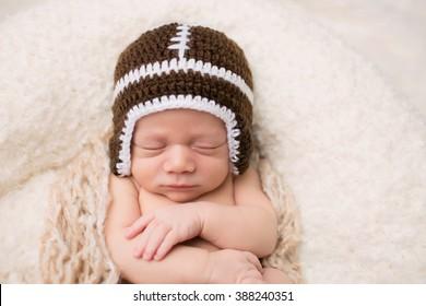 Newborn Baby sleeping on a blanket, wearing a knit football hat