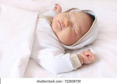 Newborn baby sleeping on white bed with copy space