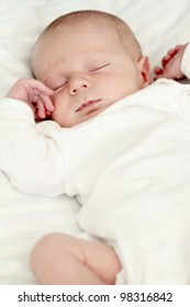 Newborn baby sleeping on white blanket. Soft focus, very shallow DOF.