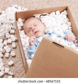 Newborn baby sleeping in open post box with filler represented on carpet. Small baby relaxing in box and dreaming about freedom.