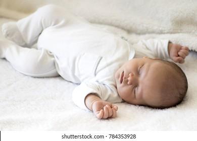 Newborn Baby Sleeping Peacefully on white blanket
